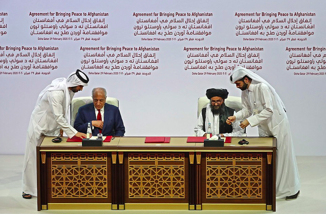 Zalmay Khalilzad and Mullah Baradar sign the US-Taliban peace agreement in the Qatari capital Doha. Credit to AFP via Getty Images