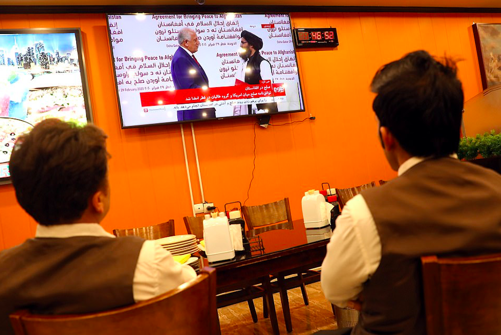 Afghans in Kabul watch a live TV broadcast at a restaurant during the signing ceremony between the US and the Taliban. Credit to Reuters