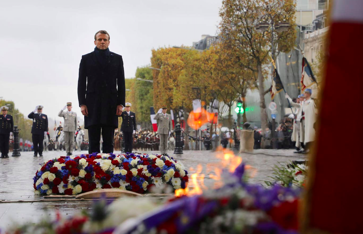 French President Emmanuel Macron stands by a wreath of flowers during a ceremony at the Arc de Triomphe in Paris 2019. Credit: POOL/AFP via Getty Images