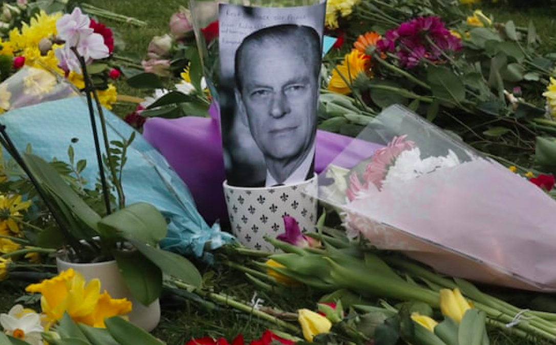 A photo of Britain's Prince Philip is among flowers left by the public outside the gates of Windsor Castle in Windsor, England. Credit to Frank Augstein/AP